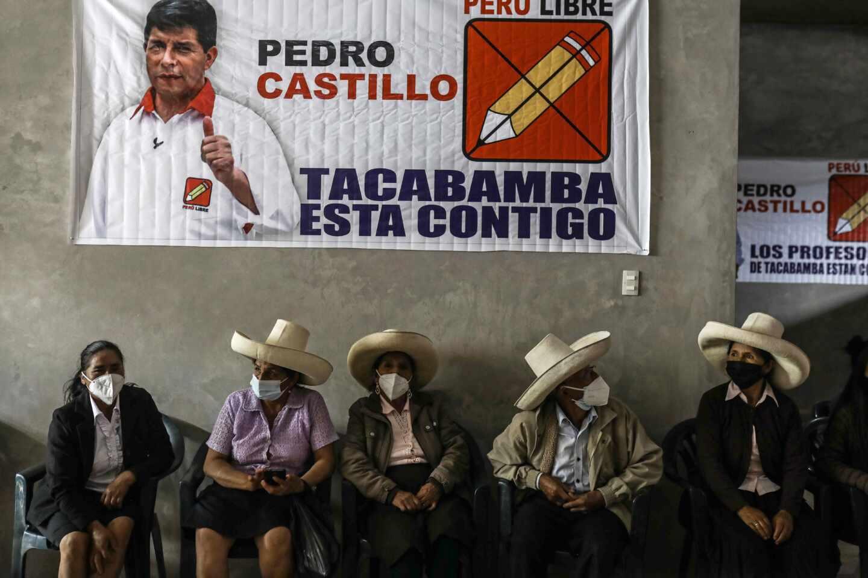 Varios peruanos está sentados bajo un cartel electoral de Pedro Castillo