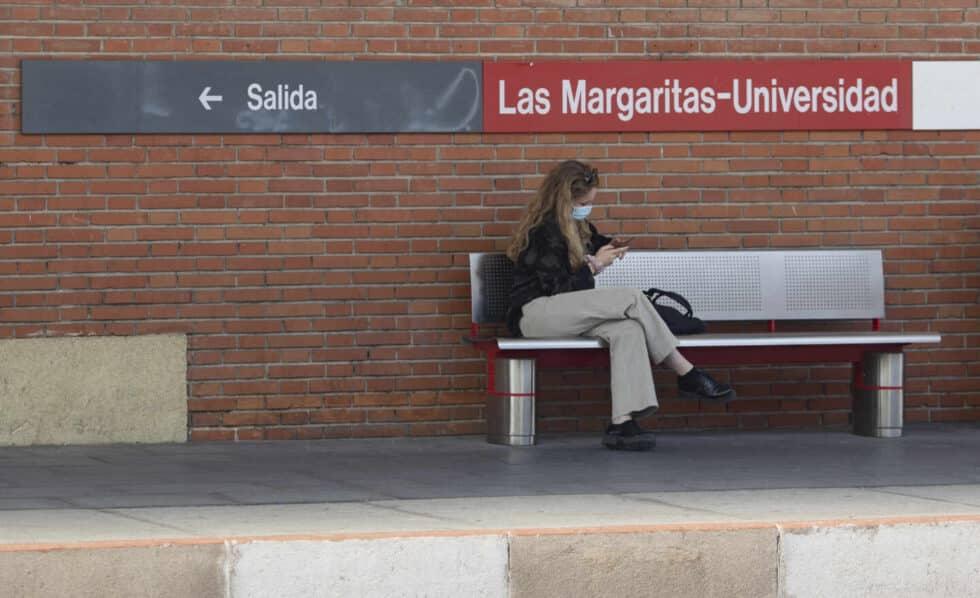 Una estudiante universitaria en un andén de una estación de tren