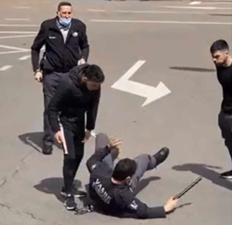 Un vigilante de seguridad en el suelo mientras los dos agresores le increpan