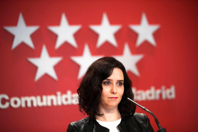 La presidenta de la Comunidad de Madrid, Isabel Díaz Ayuso, delante de una bandera de la Comunidad de Madrid.