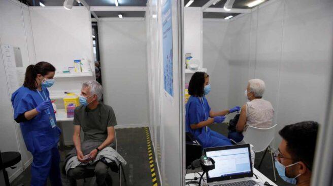 Un grupo de personas esperan a ser vacunados contra la COVID 19 en el pabellón número cuatro de la Fira de Barcelona
