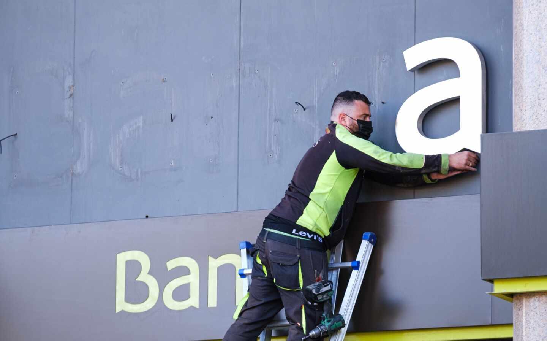 Un operario desmonta el logo de Bankia en la sede del banco en Logroño