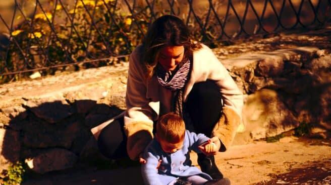 Una mujer juega con un bebé en la calle.