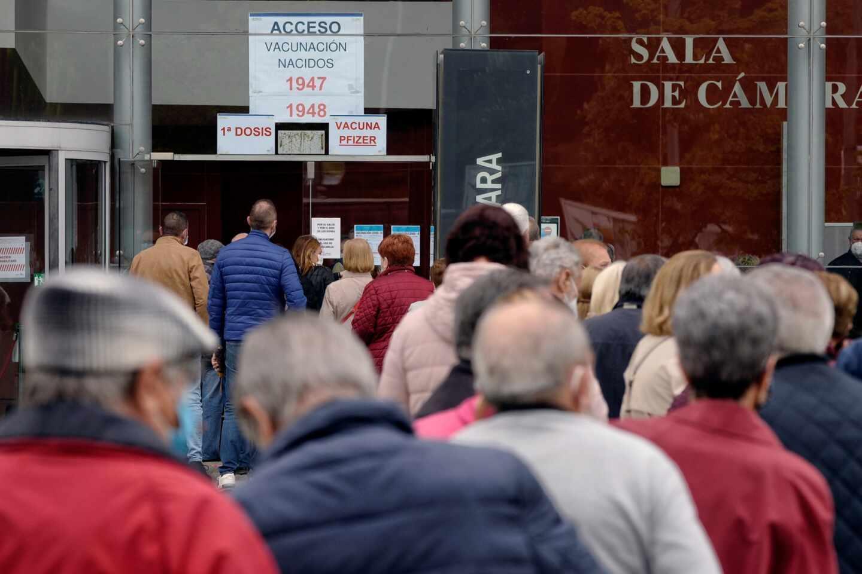 Varias personas citadas para recibir la primera dosis de Pzifer hacen cola a su llegada al centro de vacunación contra la covid-19 montada en la Sála Sinfónica Jesús López Cobos de Valladolid