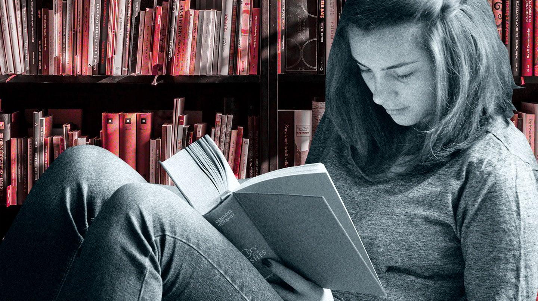 Imagen de una chica leyendo con una librería detrás