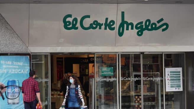 Dos personas se cruzan en la entrada de un centro comercial de El Corte Inglés.