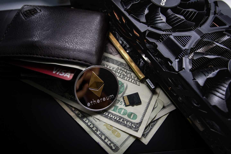 Una cartera de la que sobresalen billetes de dólares y un ethereum