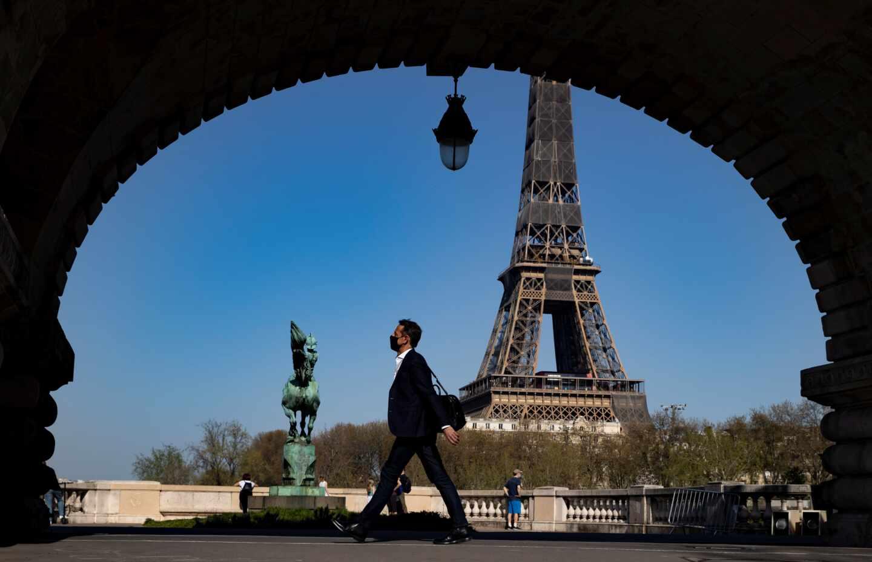 Un hombre camina en las proximidades de la Torre Eiffel.