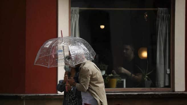 Dos personas pasan por delante de una terraza de un bar protegidos bajo un paraguas.