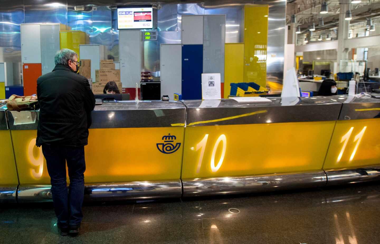 Un cliente es atendido en la oficina de Correos de Cibeles, en Madrid.