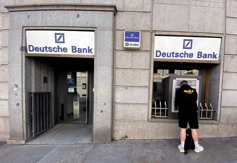 Un hombre retira dinero de un cajero Deutsche Bank.