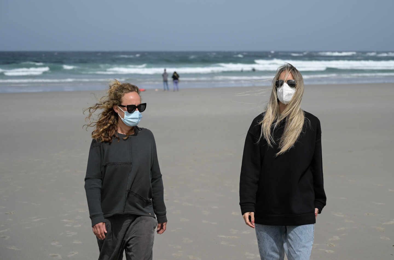 Dos mujeres, con mascarilla en la playa.