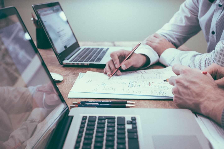Imagen de mesa de trabajo con ordenadores y papeles con datos financieros