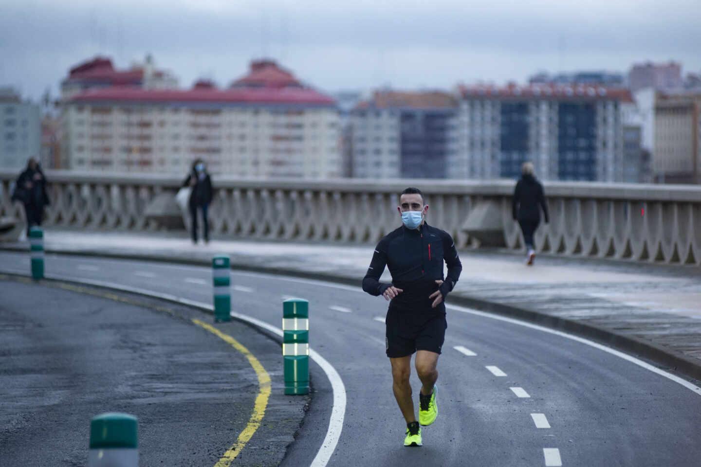 Una persona corre en solitario y con mascarilla un día en Galicia.