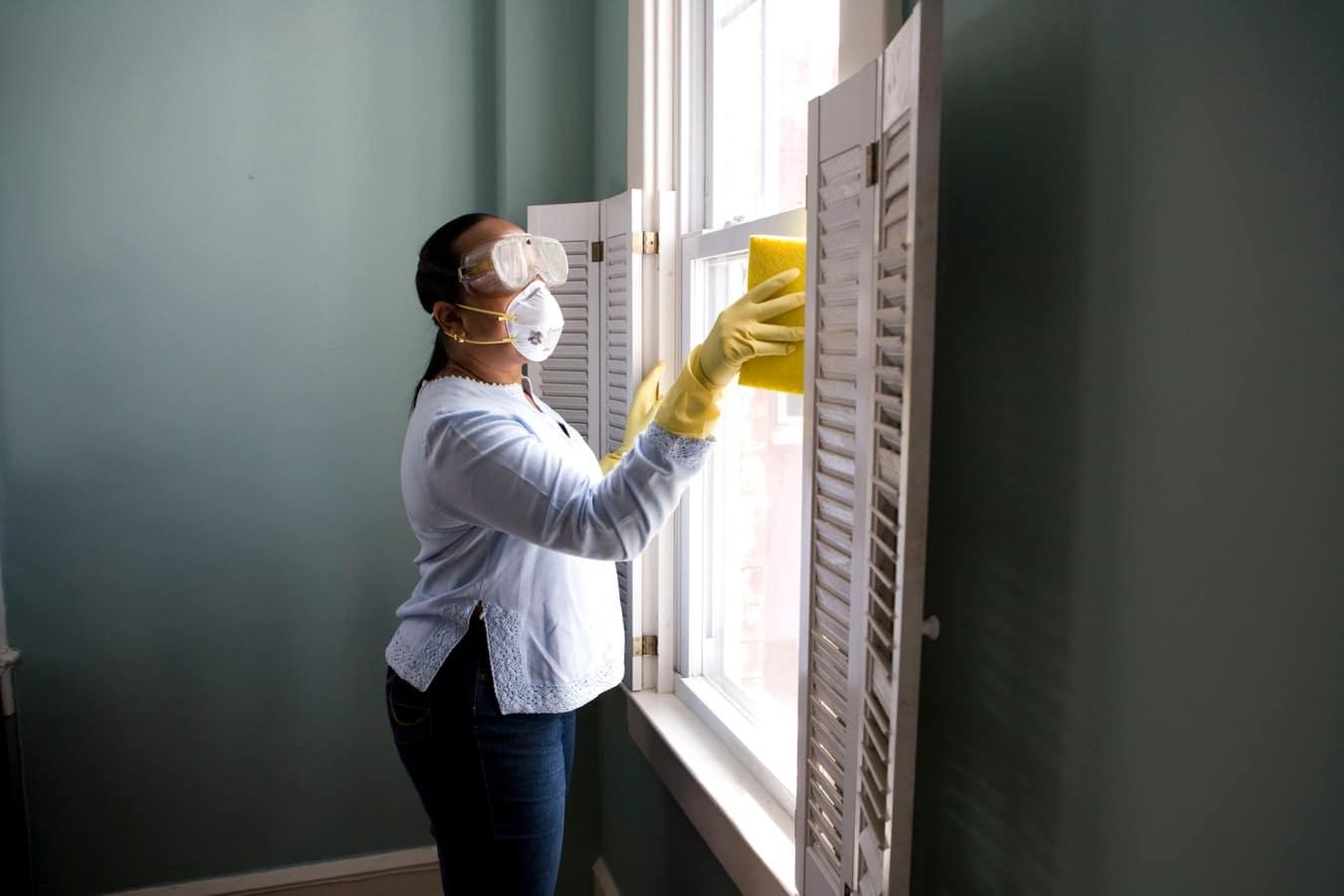 Una mujer limpia una casa equipada con mascarilla y gafas puestas.