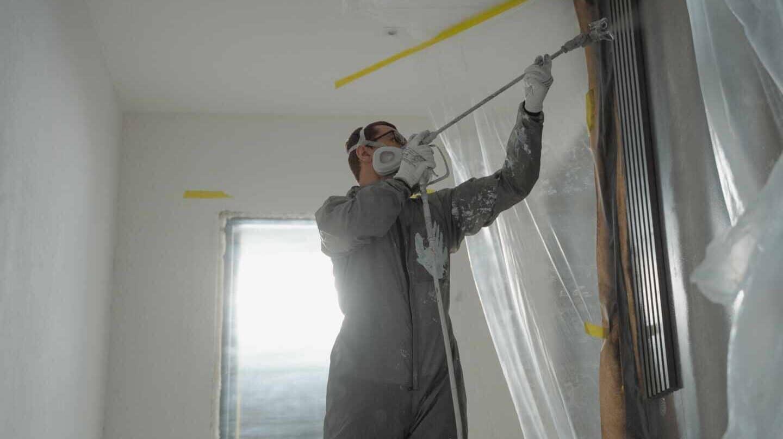 Un pintor dispara pintura en una vivienda.