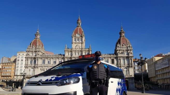 Un agente de la Policía Local de A Coruña delante de un furgón policial
