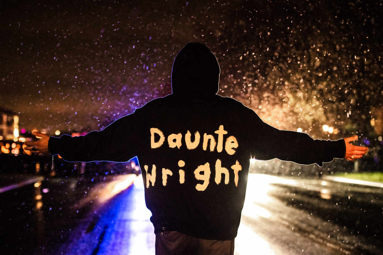 Un manifestante con el hombre de Daunte Wright en su ropa se planta ante la policía