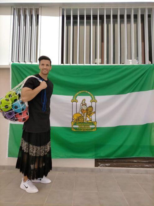 Imagen del profesor con falda junto a la bandera de Andalucía