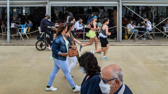 Varias personas pasean frente a un chiringuito del Paseo Marítimo de la Barceloneta hoy domingo, durante el primer día sin toque de queda en Cataluña