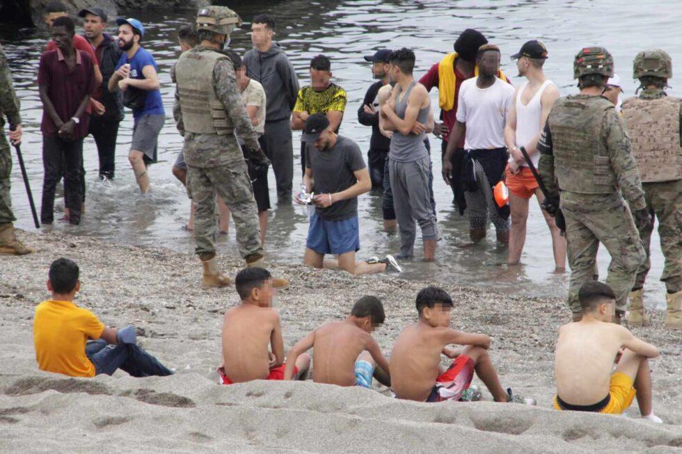 Miembros del Ejército de Tierra vigilan a un grupo de inmigrantes que han logrado cruzar uno de los espigones fronterizos de Ceuta
