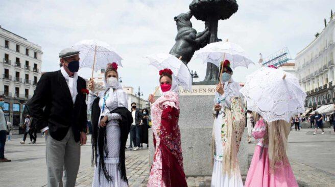 Un grupo de chulapos posa bajo el oso y el madroño en la Puerta del Sol de Madrid, el 15 de mayo de 2021.
