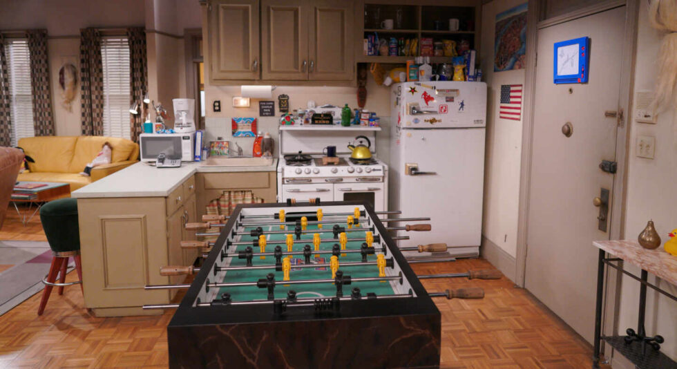 Imagen del apartamento de solteros de Joey y Chandler con el futbolín en primer plano y la cocina americana de fondo