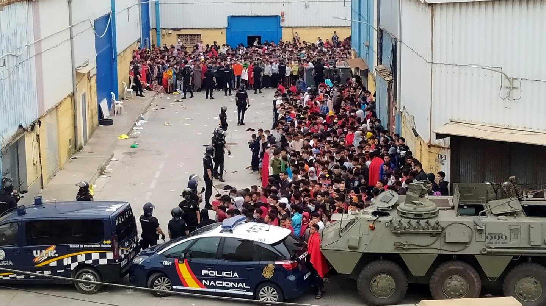 La policía Nacional y el Ejército de Tierra vigila a cientos de inmigrantes tras su llegada este martes a Ceuta
