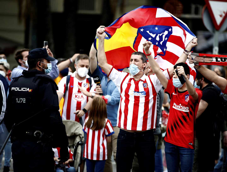 La afición del Atlético de Madrid celebra el título de Liga hoy sábado en la madrileña plaza de Neptuno