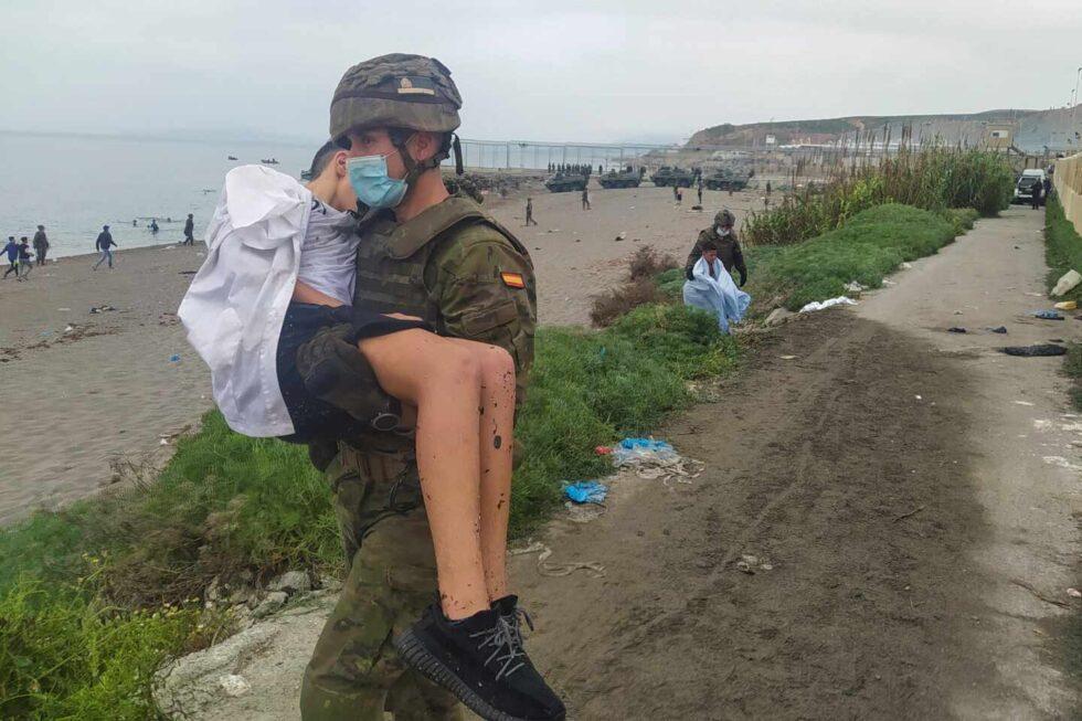 Un militar del Ejército ayuda a un inmigrante en uno de los espigones fronterizos de Ceuta