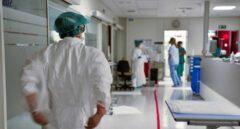 Un sanitario se coloca un traje de protección.