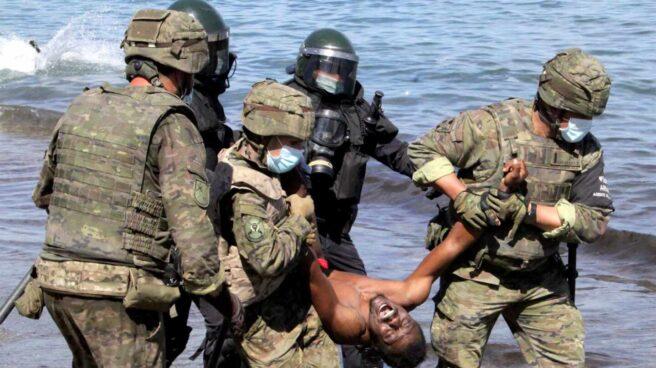 Miembros del Ejército de Tierra trasladan a un migrante que ha logrado cruzar uno de los espigones fronterizos de Ceuta