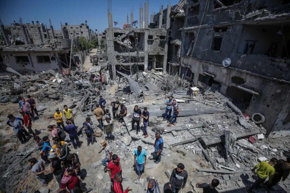 Varios palestinos inspeccionan los restos de un edificio destrozado tras los ataques