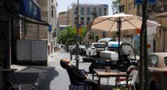 Un hombre sentado sin mascarilla en una terraza al aire libre en Jerusalén, días después de que el país eliminara el uso obligatorio de Mascarilla.