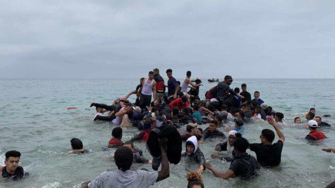 Un grupo de personas se hacen con una embarcación de las autoridades marroquíes en la playa de la localidad de Fnideq (Castillejos).