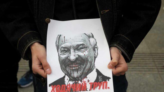 Un manifestante sostiene un cartel con la imagen de Aleksander Lukashenko, el dictador bielorruso