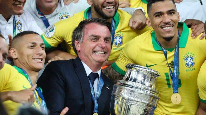 El presidente de Brasil, Jair Bolsonaro, sostiene la Copa América de 2019, rodeado de la selección nacional