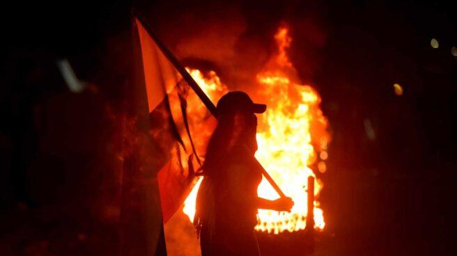 Unos manifestantes prenden fuego a unas llantas en una noche en Cali