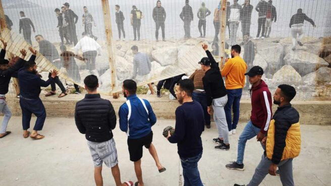 Un grupo de personas tratan de derribar la valla fronteriza en el lado marroquí