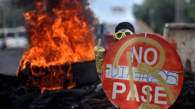 Un manifestante sostiene una señal de prohibido en una protesta contra el presidente, Iván Duque