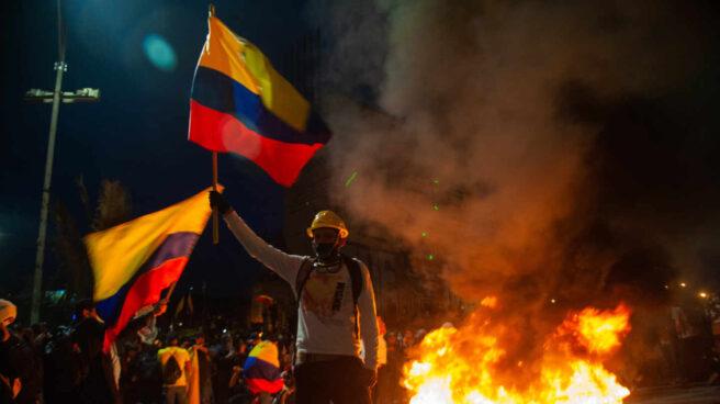 Un colombiano porta dos banderas del país en medio de las protestas en Bogotá