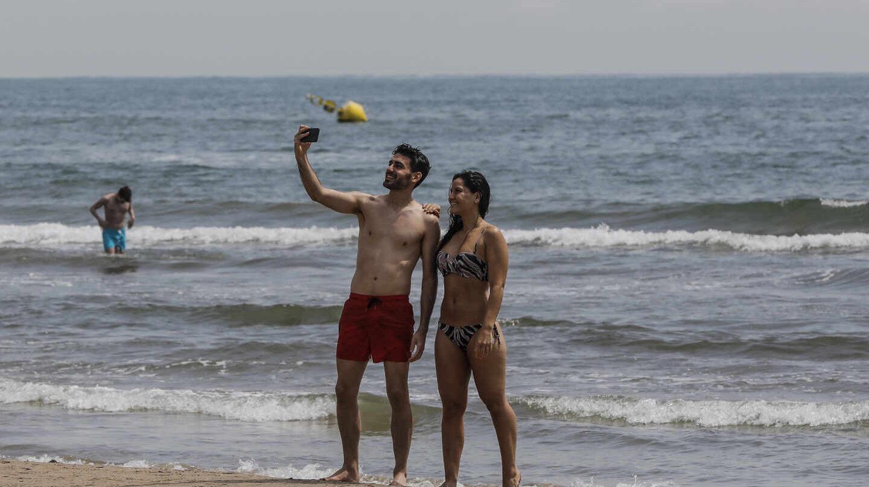 Dos personas se hacen un selfie en la Playa de la Malvarrosa.