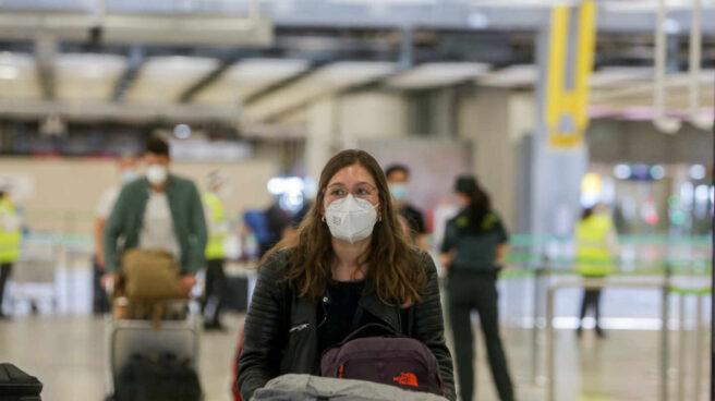 Una joven protegida con mascarilla camina por el Aeropuerto de Madrid-Barajas Adolfo Suárez.