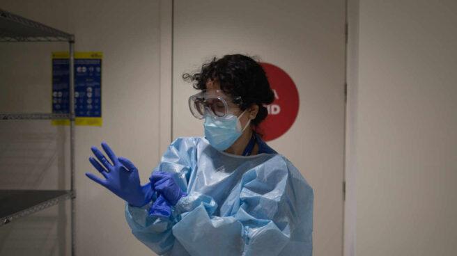 Una profesional sanitaria se viste con un Equipo de Protección Individual (EPI) en el edificio Garbí-Vall de Hebrón, en Barcelona