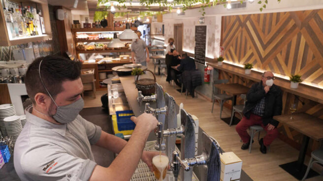 Un camarero llena un vaso de cerveza en un restaurante.
