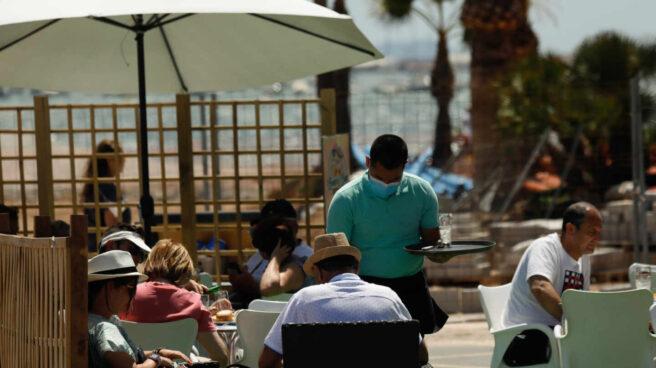 Varias personas en la terraza de un bar, frente a una playa.