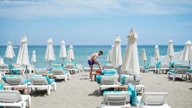 Un hombre se da crema en una playa vacía en Torremolinos, el primer día tras el estado de alarma.