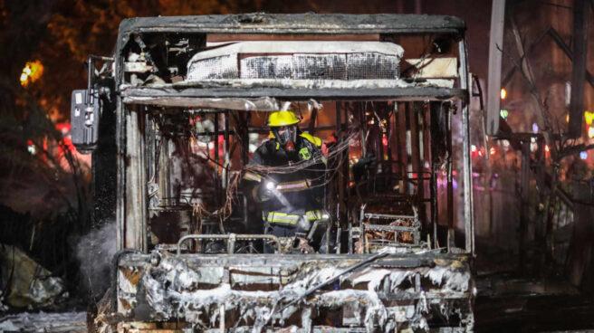 Un bombero israelí inspecciona un autobús quemado en Tel Aviv (Israel).
