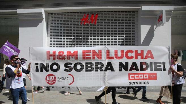 Varios trabajadores y trabajadoras de H&M se manifiestan frente a una tienda de la cadena.