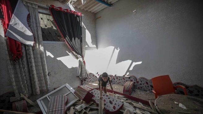 Un niño busca entre los escombros de su casa en Gaza